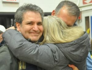 Democratic campaign manager Barbara Reynolds embraces Chris Spaulding and Brian Gordon after the election results were announced. — Gregory Menti photo